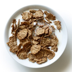Wheat bran breakfast cereal with milk in ceramic bowl. Isolated on white from above.