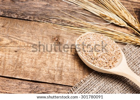 Wheat bran in wooden spoon with wheat ears. Dietary supplement to improve digestion. Source of dietary fiber. Wooden planks background. Copy space #301780091