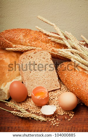 Wheat bread and grains and wheat ears with eggs on a wooden table