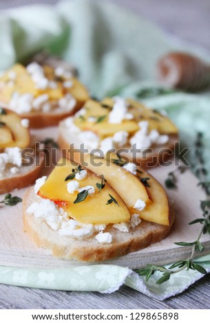 Wheat bread baguette bruschetta with salted greek feta cheese, fresh ripe nectarine slices, thyme and honey drizzling on a cutting board for snack