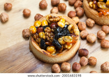 wheat dough tartlet with nuts and dried fruits in cream caramel, wheat tartlet with sweet filling, crispy tartlet with hazelnuts, peanuts and other ingredients