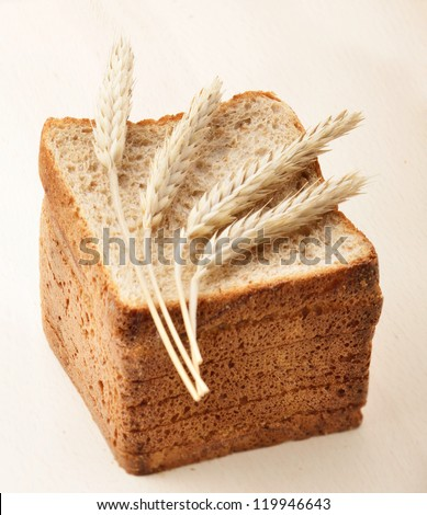 Wheat ears laid on top of a sliced bread