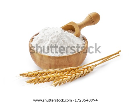 Wheat flour in bowl and spikelets isolated on white