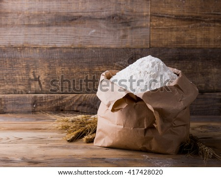 Wheat flour in Kraft paper bags. Paper packaging is on wooden background.