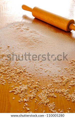 Wheat flour with a rolling pin on wooden background.