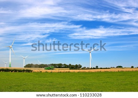 wheat harvest with combine harvester and wind turbine generating electricity