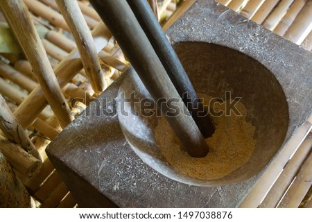 Wheat is ground in an ebony hardwood pot with an ebony rod in the village at Mount Kinabalu, Sabah, Borneo, Malaysia.