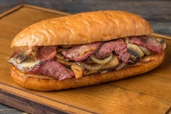 wheat loaf with barbecue beef brisket mushrooms cheese and onions on a wooden board and a dark background
