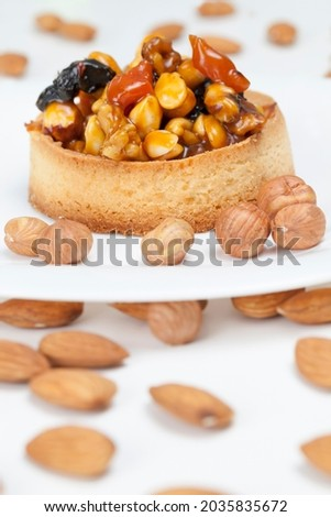 wheat tartlet with sweet filling, crispy tartlet with hazelnuts, peanuts and other ingredients, wheat dough tartlet with nuts and dried fruits in cream caramel