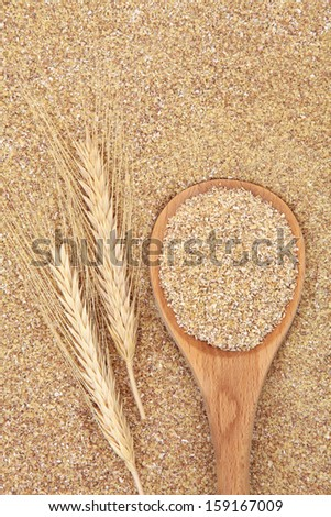 Wheatgerm in a wooden spoon with wheat ears forming a textured background. Stock photo ©