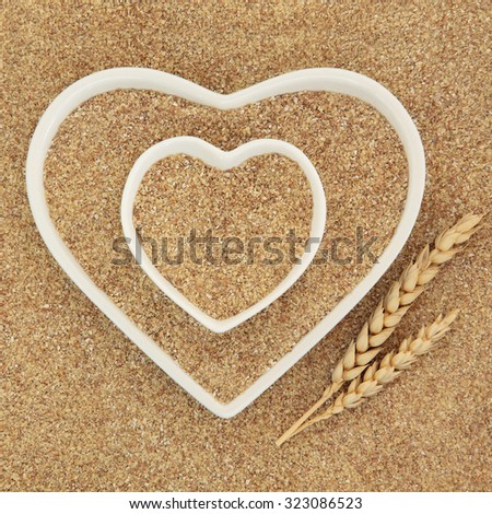 Wheatgerm in heart shaped white porcelain dishes with wheat sheaths forming an abstract background. Stock photo ©