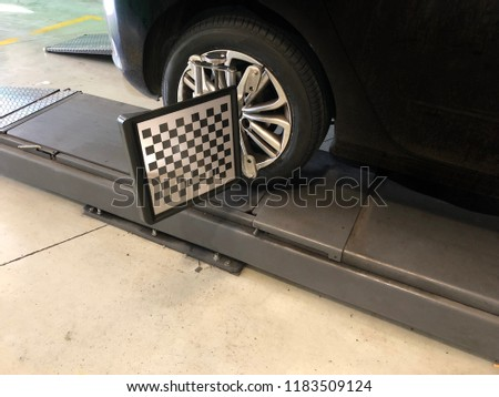 Wheel alignment in a black car. Maintenance operation for wheels in vehicles #1183509124