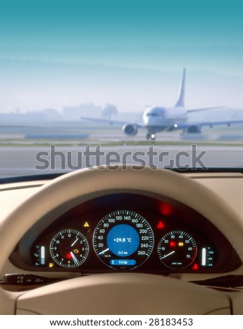 Wheel and dashboard of a car and view of airport