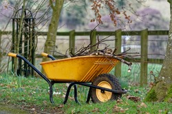 Wheel barrow made of plastic with stick and twig in the forage bucket