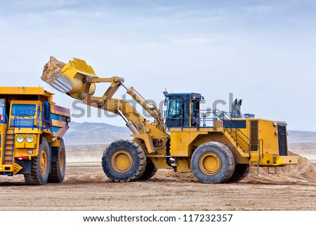 Wheel front-end loader unloading ore into heavy dump truck