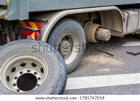 Wheel hub and truck tire in process of changing wheel nut. Maintenance a truck wheels hub and bearing. Rear wheels hub and bolt nut of a truck in process of changing wheel. Brake disc under.