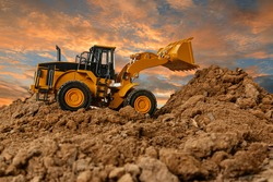 Wheel loader are digging the soil in the construction site on the  sky background after sunset