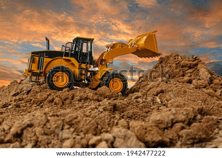 Wheel loader are digging the soil in the construction site on the  sky background after sunset Photo stock ©