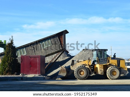 Wheel loader at construction site. Fron-end loader unloads crushed stone and unloading bulk cargo from gravel pit. Gravel  a cement production site. Stockfoto ©