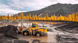 Wheel loader at work. It transports gold-bearing mountain soil to the hopper of the washing device. The gold mining industry in Eastern Siberia widely uses such equipment as front loader, bulldozers
