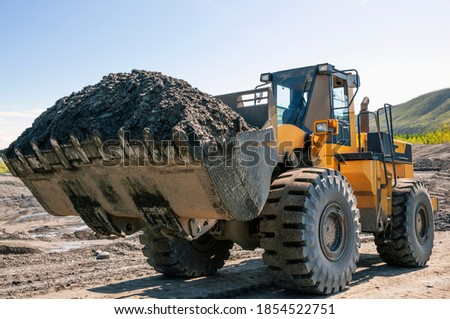 Wheel loader at work. It transports gold-bearing mountain soil to the hopper of the washing device. The gold mining industry in Eastern Siberia widely uses such equipment as front loader, bulldozers ストックフォト ©