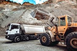 Wheel loader bulldozer with blade loading dumper trucks on construction site. Excavator details