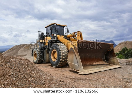Wheel loader excavator and background of crushed stone hills. Heavy equipment. ストックフォト ©