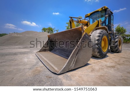 Wheel loader excavator and background of crushed stone hills. Heavy equipment. heavy construction machine in open-cast mining  #1549751063