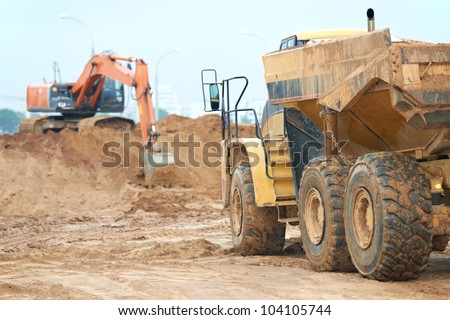 wheel loader excavator machine loading dumper truck at sand quarry