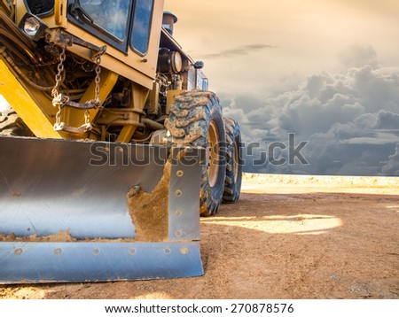 Wheel loader Excavator with backhoe unloading sand at eath works in construction site