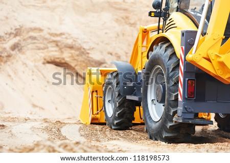 Wheel loader Excavator with backhoe unloading sand at eathmoving works in construction site quarry