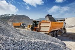 Wheel loader loads a truck with sand in a gravel pit