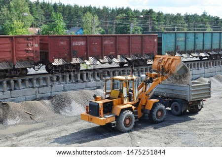 Wheel loader loads gravel into a dump truck at a cargo railway station. Fron-end loader unloads crushed stone in a gravel pit.  Unloading bulk cargo from freight cars on high railway platform Stockfoto ©