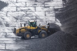 WHEEL LOADER - Machine at work on the yard of a coal storage site in rainy weather