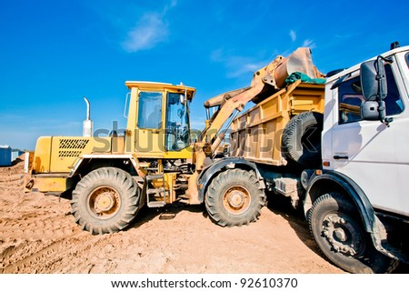 Wheel loader machine loading into dumper truck tipper soil at construction site