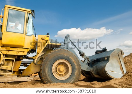 Wheel loader machine loading sand at eathmoving works in construction site over blue sky
