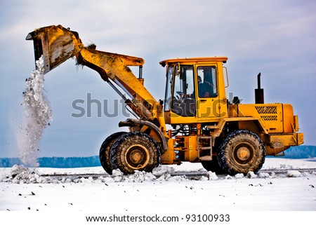 Wheel loader machine removing snow in winter on the road