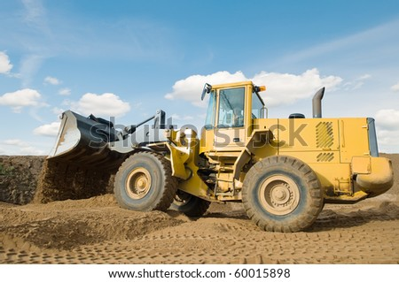 Wheel loader machine unloading sand at eathmoving works in construction site