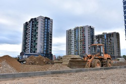 Wheel loader on road building at construction site. Earth-moving heavy equipment for road work. Tower cranes construct of modern residential buildings. Construction machinery and civil engineering