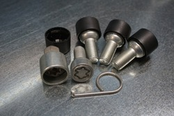 Wheel locks set against steel background.  Set of anti-theft bolts for a car on a steel background.