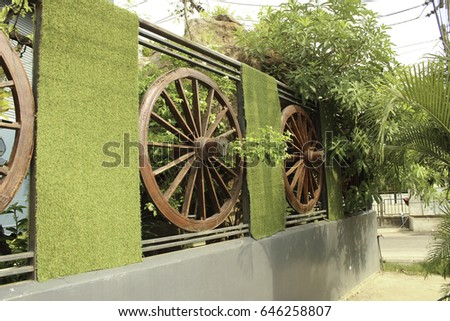 Wheel of cart to decorate the fence #646258807