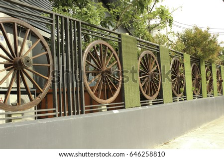 Wheel of cart to decorate the fence #646258810