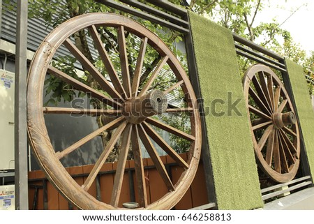 Wheel of cart to decorate the fence #646258813