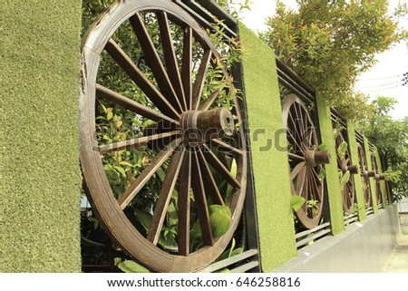 Wheel of cart to decorate the fence #646258816