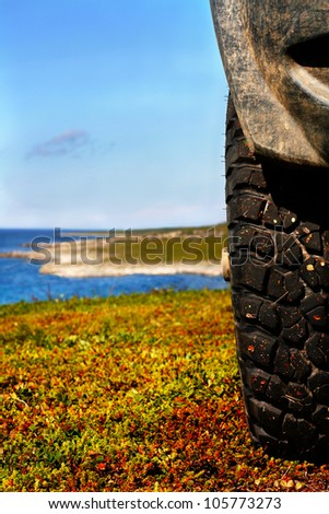 Wheel of offroad car against the  landscape of tundra coast