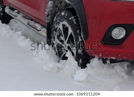 Wheel of the car stuck in the deep snow detailed  #1069211204