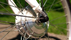 Wheel of the electric bicycle front view in sunny summer day with green grass bokeh on the background. E bike motor with light reflections. Close up.