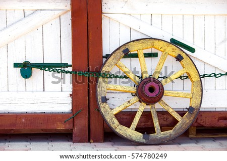 wheel of the wooden cart costs near wooden gate.