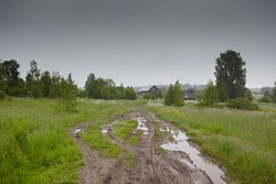 Wheel off-road track in a countryside landscape with a muddy road and puddle. Extreme path rural dirt. Summer landscape with grass and traces from the passage of transport on the surface