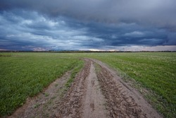 Wheel off-road track in a countryside landscape with a muddy road. Extreme path rural dirt. Spring landscape on a background of a dark blue rainy sky